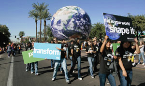 Students marching in homecoming parade carrying signs promoting sustainability and a big globe of the earth.