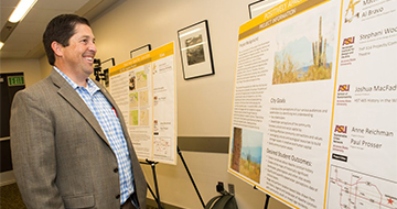 Man smiling and looking at project cities posters