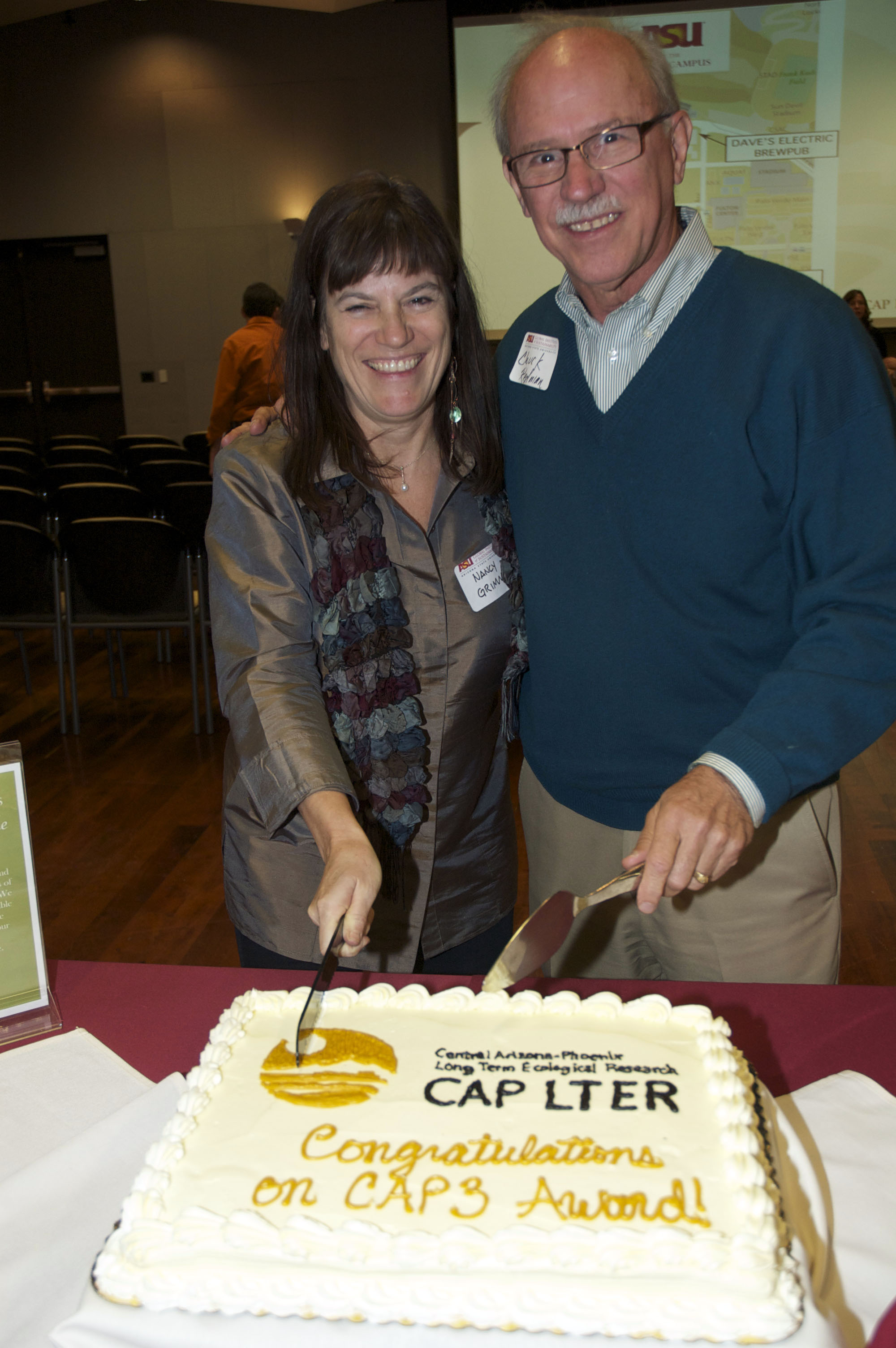 Former co-directors Nancy Grimm and Charles Redman cut a cake celebrating a new grant from NSF.
