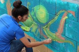 student helps to paint sustainability mural