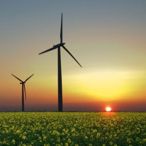 Landscape view of sunset with two wind mills over green pasture