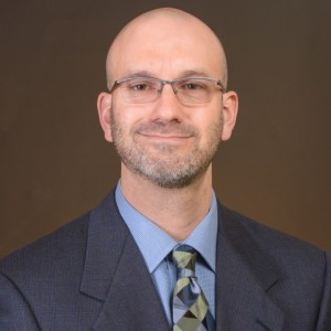 researcher Joshua Abbott wearing glasses and a blue suit