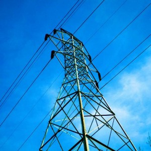 Electrical towering looming in front of a bright blue sky