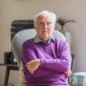 Sir Crispin Tickell wearing purple sweater sitting in arm chair in sunlit room