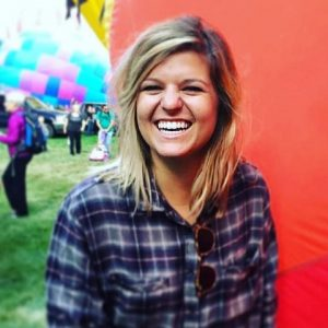 Kayla Bellman laughing in front of red hot air balloon