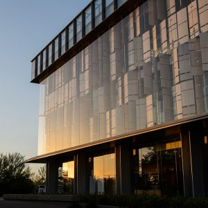 The modern glass aesthetic of ASU's Biodesign building reflecting the sunset
