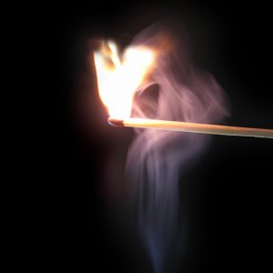 Lit match in front of black background