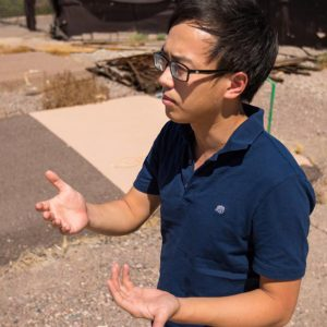 Man wearing glasses and navy shirt, standing in the Arizona sun