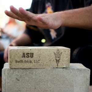 A hand hovers above a sample of the sustainable building material, BetR-blok