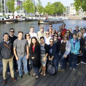 Group of smiling adults standing by a European riverfront
