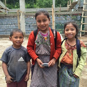 Young students stand in front of bottle school that is under construction