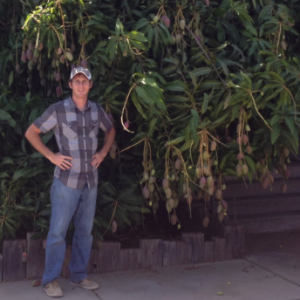 jason-tibbetts-standing-in-front-of-green-leafy-tree
