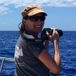 Dr. Gerber holding binoculars, doing field research on boat at open sea