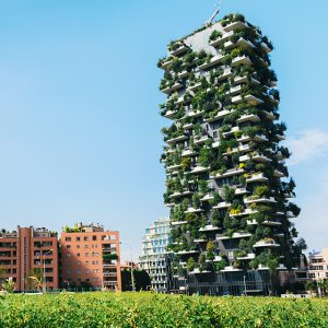 A green building towers over conventional buildings