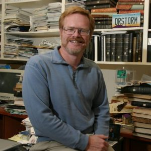 Dr. Randy Cerveny sits in his office with books piled behind him.