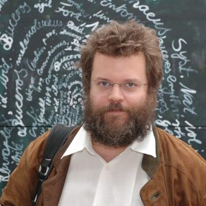 Manfred wearing a brown jacket and standing in front of a chalkboard full of writing