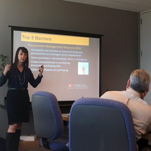 """Nicole Darnall in front of a projector screen that reads """"Top 5 Barriers"""""""