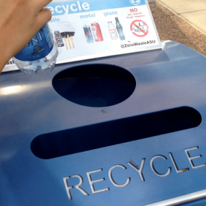 Someone throws a plastic water bottle into a blue recycling container.