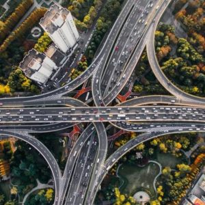 Series of highways connecting over a city and large green space. Many cars on the highways.