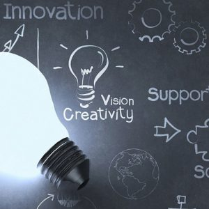 "Light bulb against blackboard that reads ""innovation, vision creativity, support"""