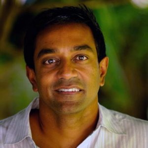 Headshot of M. Sanjayan against green leafy background