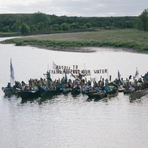 Indigenous people in boats on a lake with a sign to protect the water.