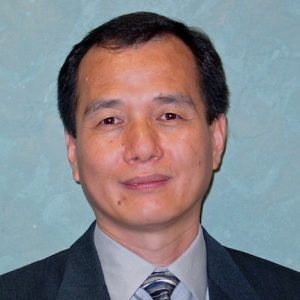 Meng Tao sits for a portrait, dressed in a suit and a striped blue tie.