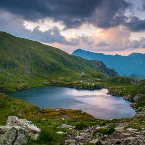 Landscape of mountains and small lake with stormy sunset sky