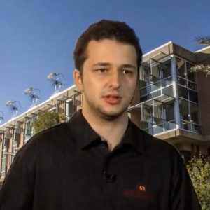 Alen Jakupovic sits in black polo in front of Wrigley Hall backdrop.