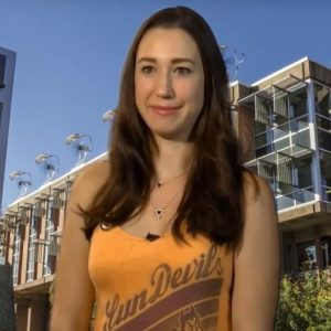 Leah Sunna sits in yellow ASU tank top in front of Wrigley Hall backdrop.