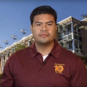 Marco Ugarte sits in maroon SOS polo in front of Wrigley Hall backdrop.