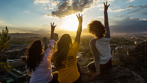 sustainability students raise their sun devil forks in front of a sunset